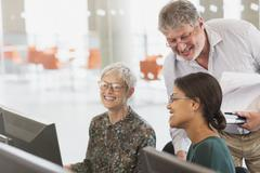 Smiling students talking at computer in adult education classroom - stock photo