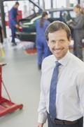 Portrait smiling businessman in auto repair shop Stock Photos