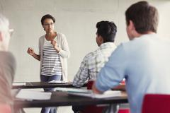 Teacher speaking to students in adult education classroom - stock photo