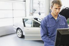 Mechanic working at computer in auto repair shop Stock Photos