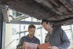 Mechanics with clipboards talking under car in auto repair shop Stock Photos