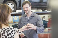 Mechanic taking keys from woman in auto repair shop Stock Photos
