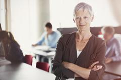 Portrait of confident senior woman in adult education classroom - stock photo