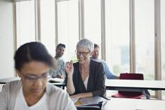 Smiling senior woman studying in adult education classroom - stock photo