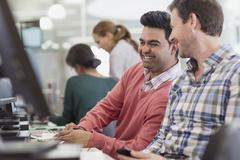 Stock Photo of Men laughing at computer in adult education classroom