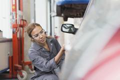 Female mechanic examining car in auto repair shop Stock Photos