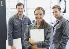 Portrait confident female mechanic with clipboard in auto repair shop Stock Photos