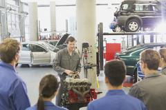 Mechanic explaining car engine to students in auto repair shop Stock Photos
