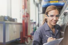 Portrait confident female mechanic with clipboard in auto repair shop - stock photo