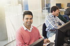 Portrait smiling adult education student at computer in classroom Stock Photos