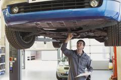 Mechanic with clipboard working under car in auto repair shop Stock Photos