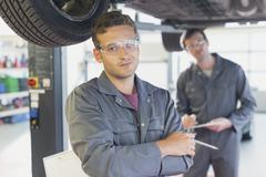 Portrait confident mechanic under car in auto repair shop Stock Photos