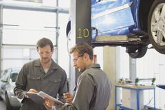 Mechanics reviewing paperwork in auto repair shop Stock Photos
