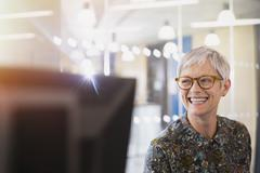 Enthusiastic senior businesswoman looking away in office Stock Photos