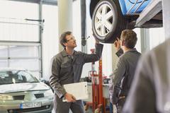 Mechanics examining and discussing tire in auto repair shop Stock Photos