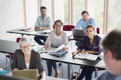 Smiling students watching teacher in adult education classroom - stock photo