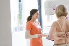 Nurse helping patient prepare for mammogram - stock photo