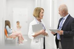 Doctor and administrator with digital tablet talking in hospital corridor Stock Photos