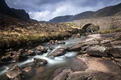 Stream flowing under remote aqueduct, Scotland Stock Photos