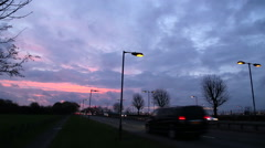 Cars pass on busy road next to heathrow airport at dusk with sunset Stock Footage