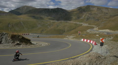 View of four longboarders speeding in curves and one man walking on Transalpina Stock Footage