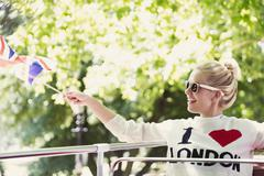 Smiling woman waving British flag on double-decker bus - stock photo