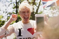 Stock Photo of Enthusiastic woman waving British flag being photographed