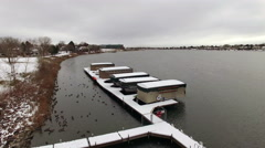 Aerial drone fly over lake snow covered boating dock covers secured for the - stock footage