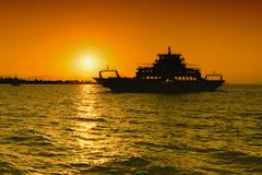 Ferry boat silhouette against the sunset. - stock photo