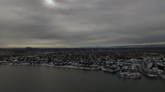 Aerial drone pan left dark gray cloud city over windy lake. Stock Footage