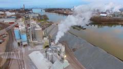 Factory smokestack smoke or steam with railroad bridge, aerial Stock Footage
