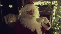 Stock Video Footage of Santa Claus drinking cup of hot tea / coffee, decorated fireplace on background