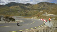 View of three longboarders riding on a beautiful day on Transalpina Stock Footage