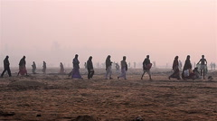 Wide shot of village people walking towards river in the morning. - stock footage