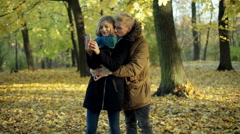 Couple cuddling in the park and doing photos on smartphone - stock footage