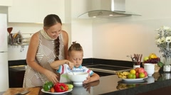 Mother and son cooking a salad in the kitchen - stock footage