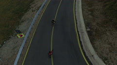 Aerial view of four men longboarding on the famous Transalpina road Stock Footage