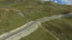 Aerial view of four longboarders going down the Transalpina road Stock Footage