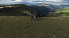 Aerial view of four men walking on the edge of Transalpina Stock Footage