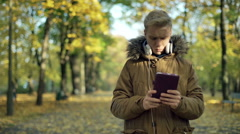 Man using selfiestick and recording on smartphone in the park Stock Footage