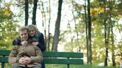 Couple cuddling and showing thumbs to the camera in the park - stock footage
