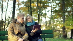 Couple browsing internet on tablet in the autumnal park Arkistovideo