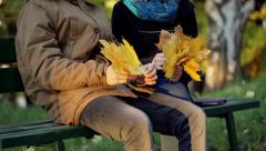 Couple sitting on the bench in the autumnal park and holding bunch of maple leav Stock Footage