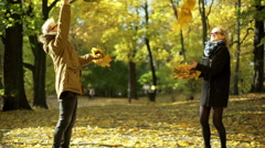 Stock Video Footage of Couple throwing maple leaves in the autumnal park and having fun