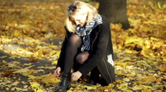 Girl squating in the autumnal park and tying shoe laces Stock Footage