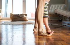 Mother walking at home with child standing on her feet - stock photo
