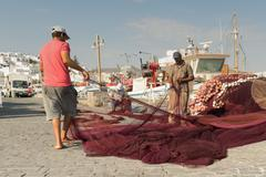 Fishermen on their morning routine job at Paros island in Greece. - stock photo