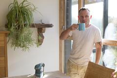 Wood joiner enjoying a tea break - stock photo