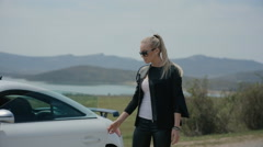 Confident woman on the road beside her expensive car Stock Footage