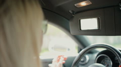 Self-confident woman looks in the mirror in the car - stock footage